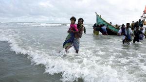 Flyktingar från Burma anländer till Bangladesh vid stranden av floden Naf.