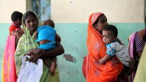 Mammor köar för vård för sina barn på ett sjukhus i Calcutta