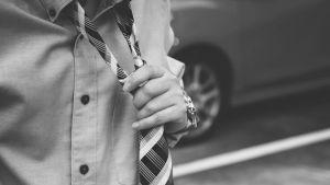 Man rättar till slipsen