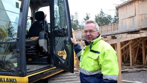 En man i arbetskläder står vid en grävmaskin.