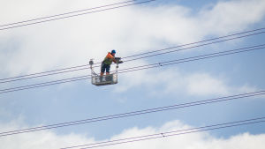 Elektriker jobbar med högspänningsledningar.