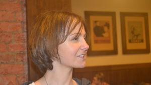 Alexandra Polivanova inomhus i ett kafé med tegelväggar