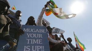 """Demonstranter i Zimbabwe med en skylt med texten """"Mugabe your time is up""""."""