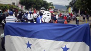 Demonstration i Tegucigalpa. Folk marscherar i en lång rad med flaggor.