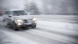 Auto ajaa lumipyryssä.