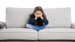 En ung flicka sitter på en ljus soffa. Hon lutar huvudet i händerna och ser uttråkad ut.