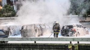 Brandmän har sprutat släckningspulver på en handfull bilar som fortfarande ryker efter brand.