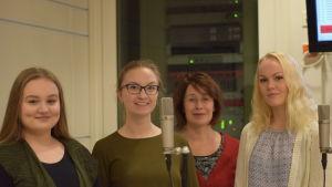 Andrea Degerlund, Emilia Ekström, Marianne Maans och Anna Malmsten står framför två mikrofoner i en studio.