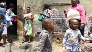 Kvinnor och barn står utanför ett övergivet hus i Zimbabwe.