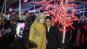 Ett par poserar under ett massbröllop i Jakarta på nyårsafton.