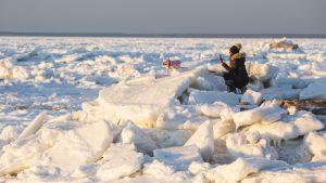 En kvinna är ute på isen med sin hund i Massachusetts.