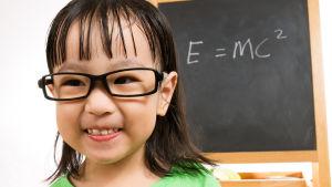 Asiatisk liten flicka framför skoltavla med Einsteins formel för relativitetsteorin E = MC2