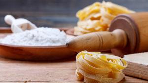 Pasta (tagliatelle), en kavel och i bakgrunden ett fat fyllt av vitt vetemjöl.