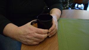 Händer som håller i en kaffekopp.