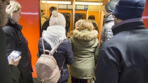Ihmisiä menossa metrojunaan   metroasemalla.