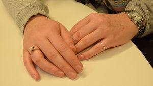 Kvinnohänder på bordet med ringar.