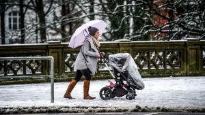 En kvinna skuffar fram en barnvagn på de snöiga gatorna i Hamburg den 18.1.2018.