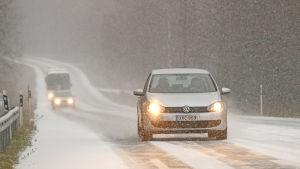 Bil kör fram längs väg i snöyra.