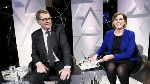 Matti Vanhanen och Tuula Haatainen sitter bredvid varandra och ler.