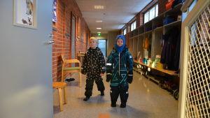 Barn med ytterkläder på i en skolkorridor.