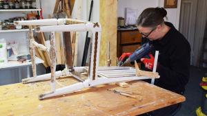 En kvinna sitter och restaurerar en vit stol.