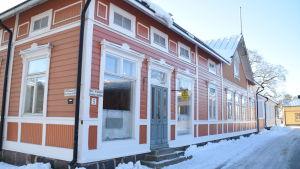 En bild på ett hus som är orangerött och som ligger i gamla stan i Ekenäs. Huset har stora fönster och landskapet runt det är täckt av snö. Huset har en grå dörr.