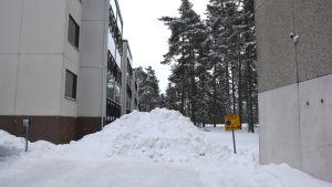 Bild på en snöhög på en parkeringsplats, brevid snöhögen finns ett märke som visar räddningsväg.