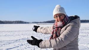 En kvinna står vid en snöklädd och isklädd sjö.