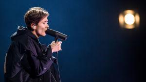 Man i profil sjunger in i stor mikrofon
