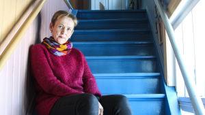 Punainen villapaita päällään oleva kuvittaja Virpi Talvitie istuu siniseksi maalatuilla portailla.