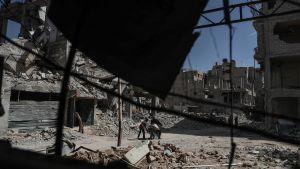 Folk vandrar igenom den sönderbombade stadsdelen Dhouma i Östra Ghouta.