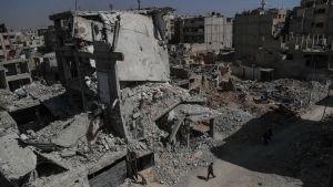 En man vandrar i den sönderbombade stadsdelen Dhouma i Östra Ghouta.