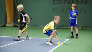 Barn övar sig på tennis.
