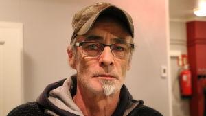 En man med keps och glasögon.