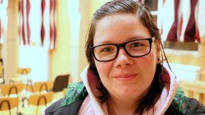 En kvinna med glasögon.