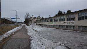 Låg tegelbyggnad intill väg 110 till St. Karins i gråmulet vinterväder