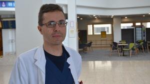 erno lehtonen-smeds står i aulan av vasa centralsjukhus. han bär vit rock och glasögon.