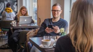 Thomas Kinnaird käyttää älypuhelinta kahvila Bergga:ssa.