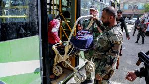 Syriska regeringssoldater hjälpte civila med att lyfta deras ägodelar i bussar som tar dem norrut, till Idlib
