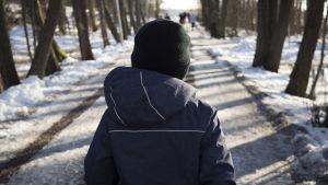 Lapsi kävelee ulkoilureitillä.