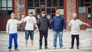 Viisi nuorta miestä hiphop-vaatteissa kuvattuna vanhan veturitallin ovien edessä