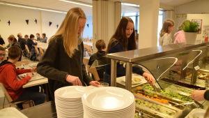 Amanda Juselius och Julia Kallioinen tar mat åt sig i Källhagens skolas matsal i Virkby.
