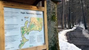En informationsskylt där det står Hagen-Ramsholmen-Högholmen ovanför en karta. Till höger om skylten syns en stig.