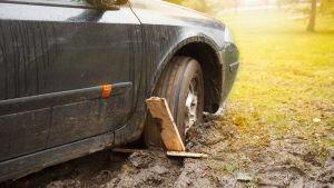En bil har fastnat med ett hjul i lera.