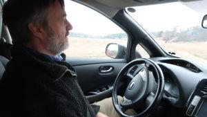 Kurt Andersson sitter inne i sin elbil. Utanför ett landskap med åker i gråmulet vårväder.