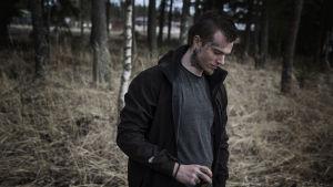 David står i en skog och tittar ner mot marken med ett litet leende på läpparna.