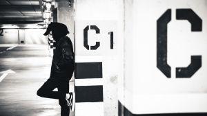 Ung man står i ett parkeringsgarage lutar sig mot en betongstolpe.