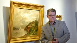Museichef Dan Lindholm fotograferad bredvid en tavla av Hjalmar Munsterhjelm.