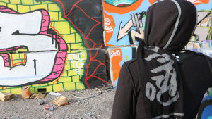 En person står framför en vägg målad med graffiti.