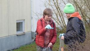 två pojkar med plastpåsar